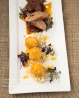 A tasting plate of duck and prune sausages and risotto balls